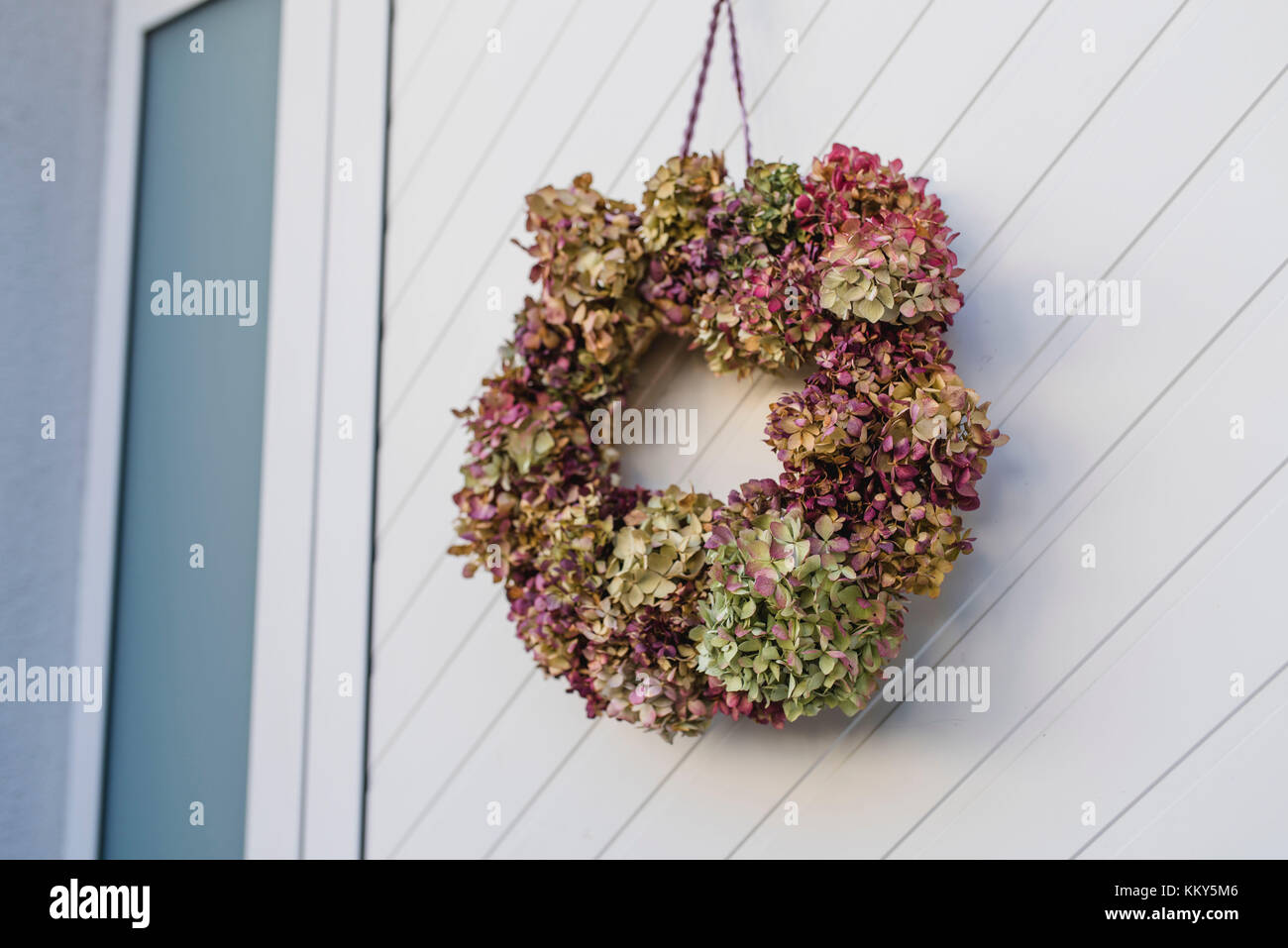 Still life, front door, detail, autumnal decoration, wreath with hydrangea blossoms, - Stock Image