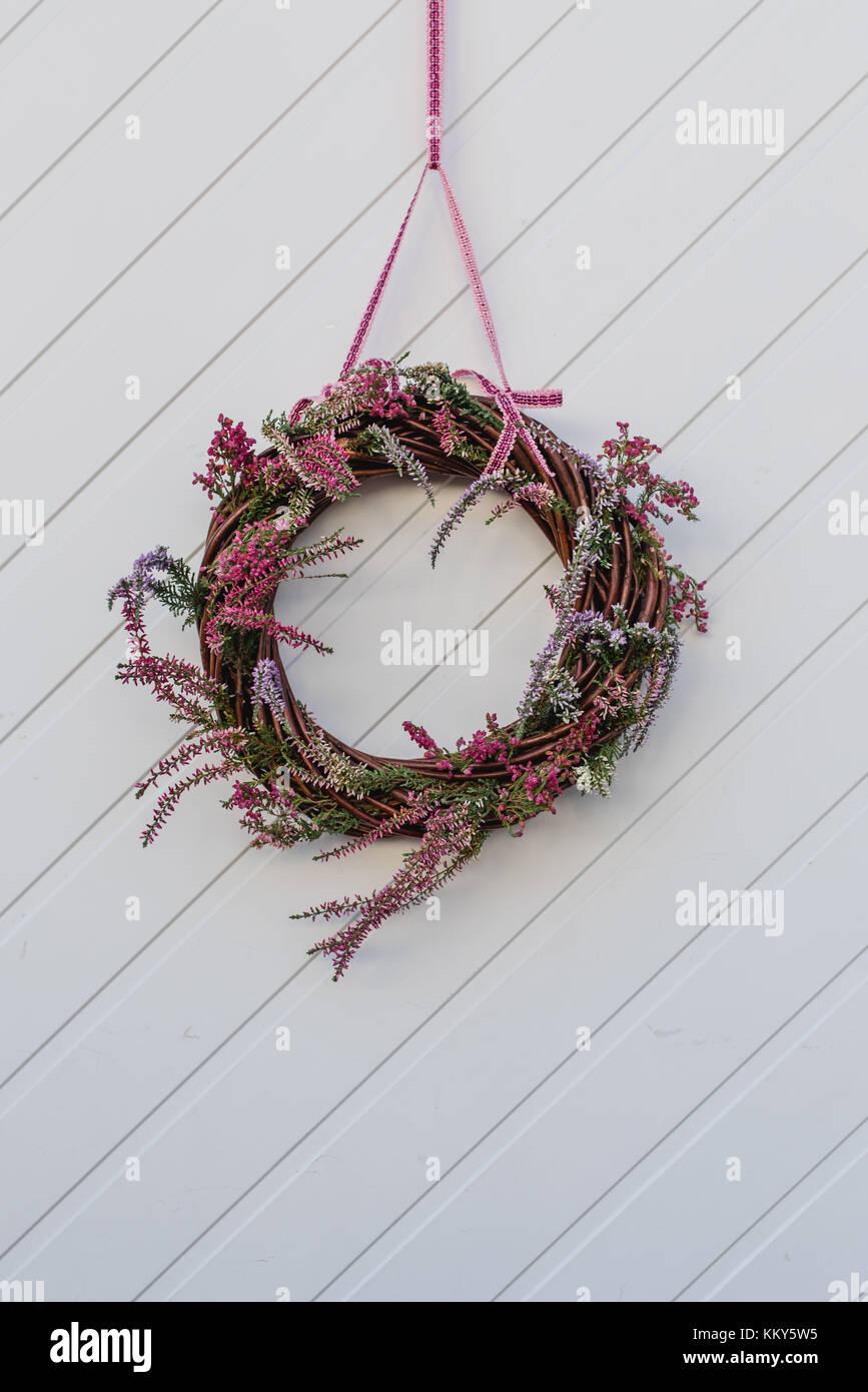 Front door, detail, autumnal decoration, willow wreath, heather - Stock Image