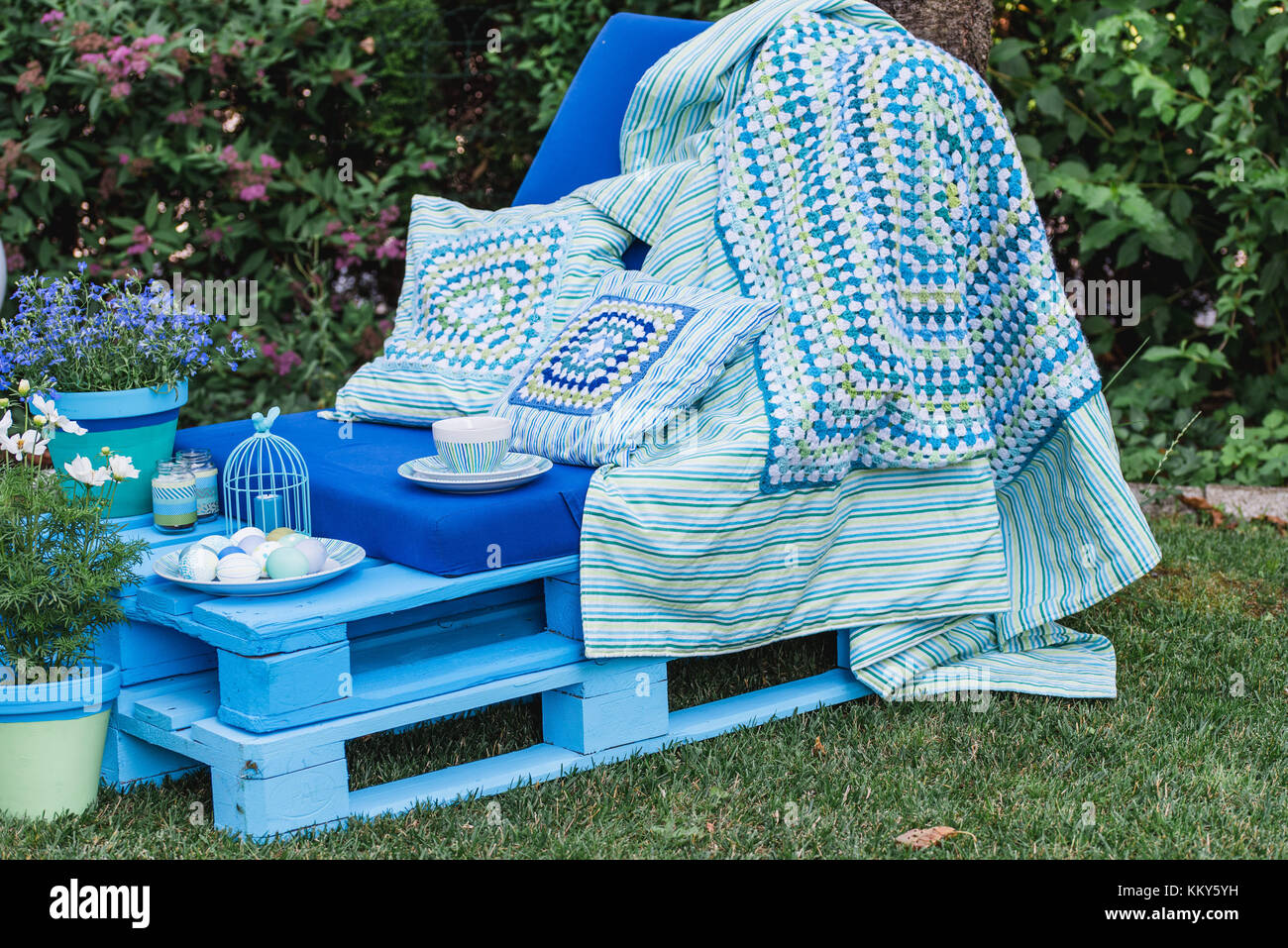 Garden, sofa made of pallets, Easter decoration, flowers, - Stock Image
