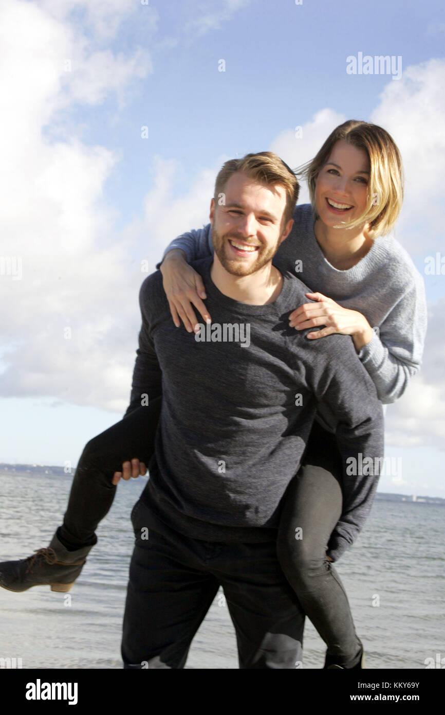 Couple, Baltic Sea beach, walk, piggyback, - Stock Image