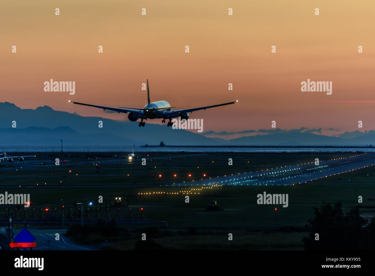 A beautiful landing of an airplane on the runway in a modern airport - Stock Image