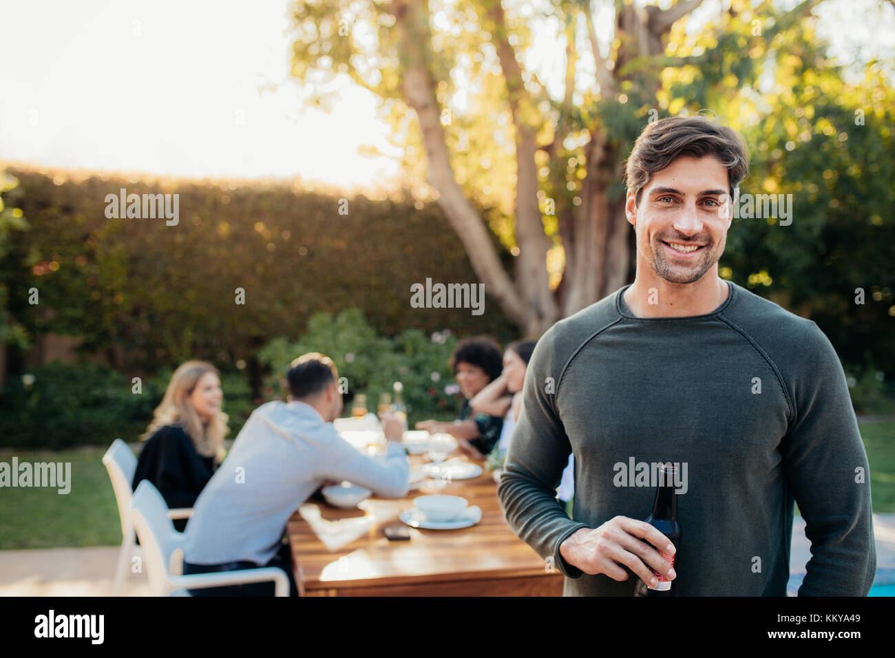 Handsome young man standing outdoors with friends sitting in background having food. Man with beer at outdoor party. - Stock Image