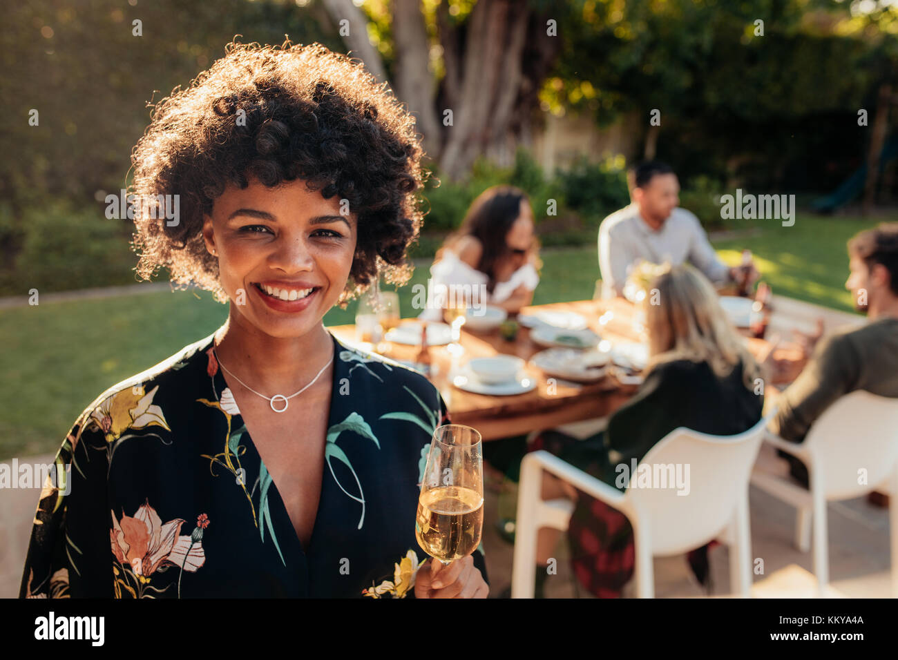 Smiling african woman standing outdoors with people sitting in background having food at party. Woman with a drinks - Stock Image