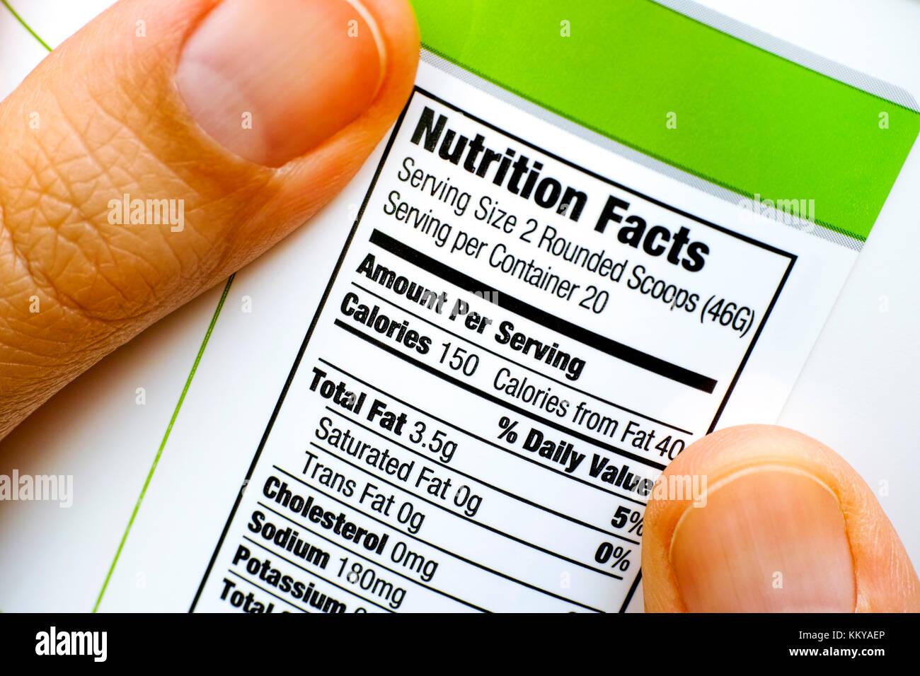 Woman fingers with protein jar. Reading nutrition facts. Closeup. - Stock Image