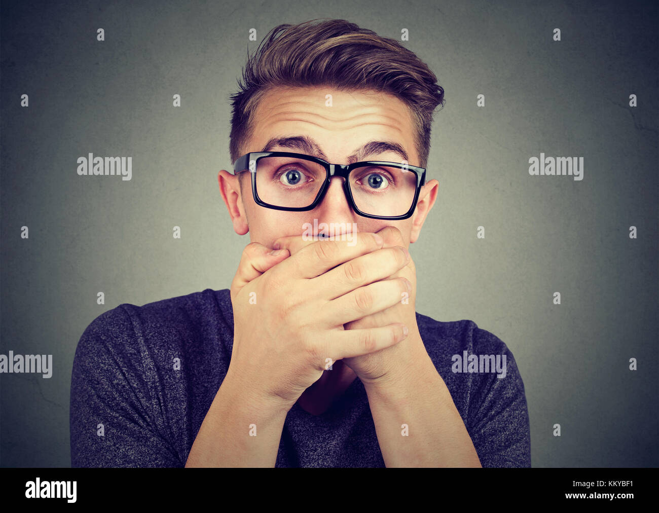 Portrait of a shocked young man covering his mouth with hands - Stock Image