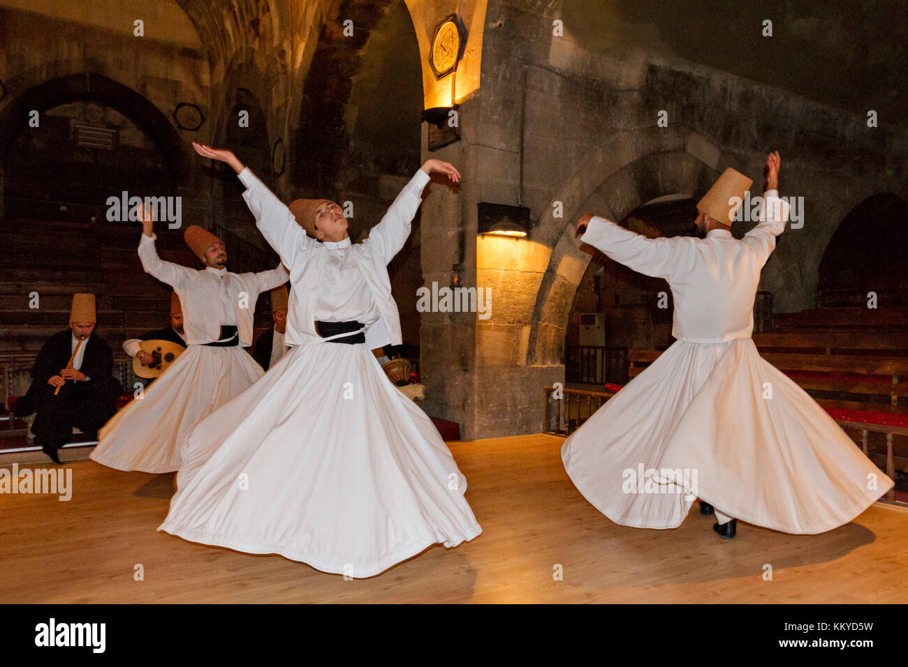 Whirling dervishes performing in an old caravansary in Nevsehir, Turkey. - Stock Image