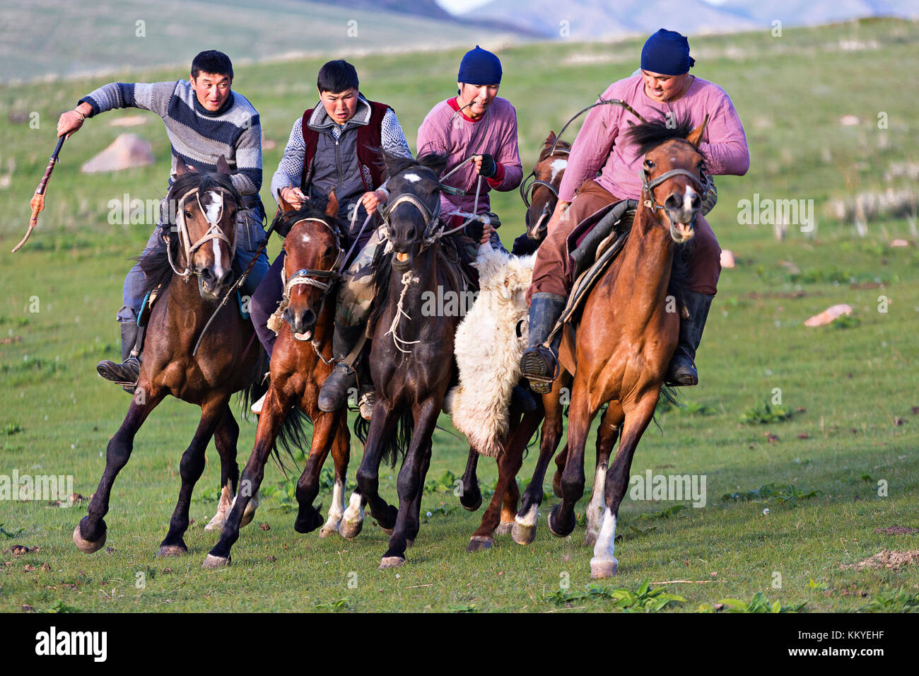 Nomadic horse riders grabbing goat carcass from each other, during traditional horse games known as Buzkashi or - Stock Image