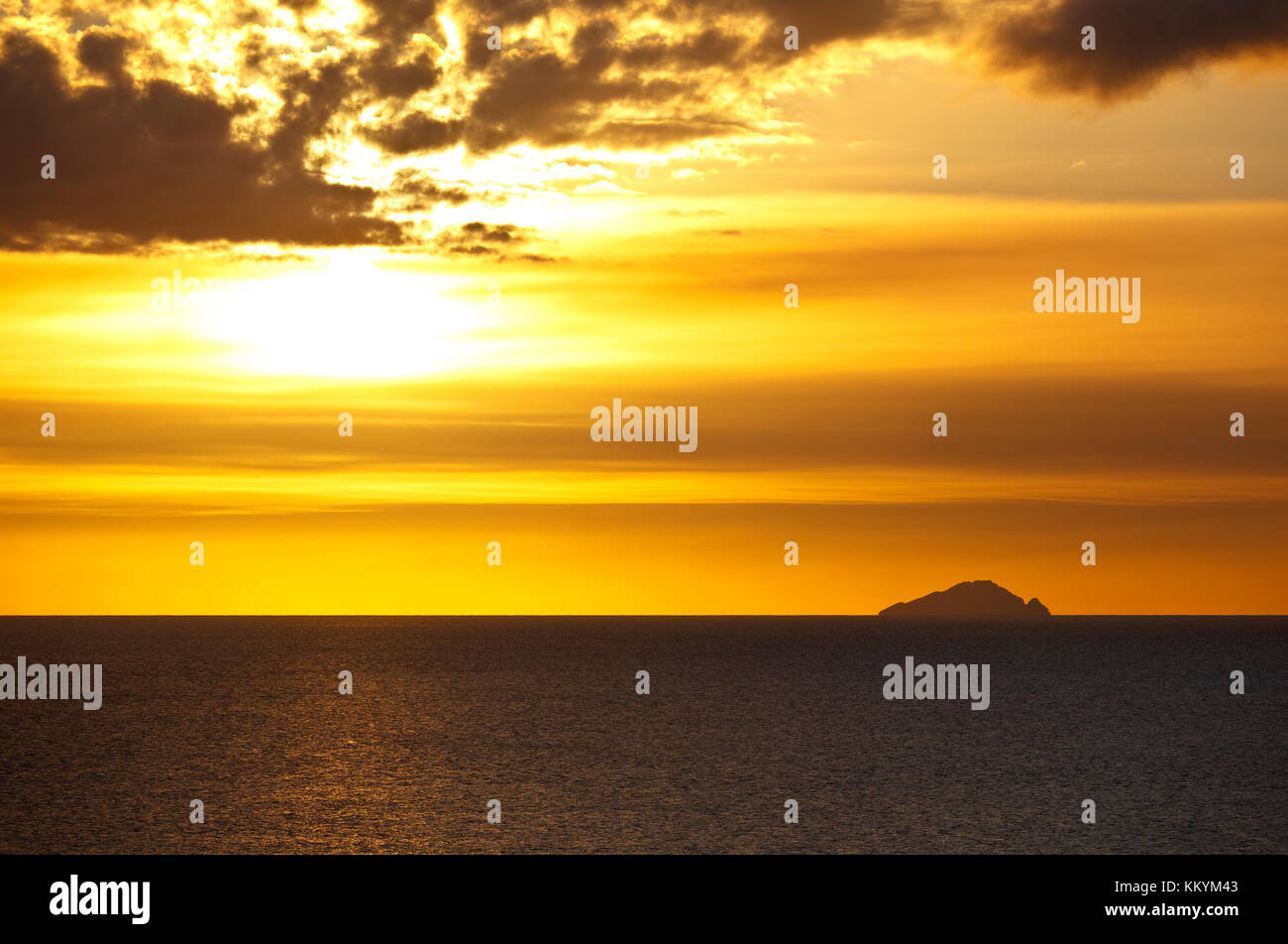 View from Antigua to the island of Redonda at sunset. The ash clouds in front of the sun are from the Soufriere - Stock Image