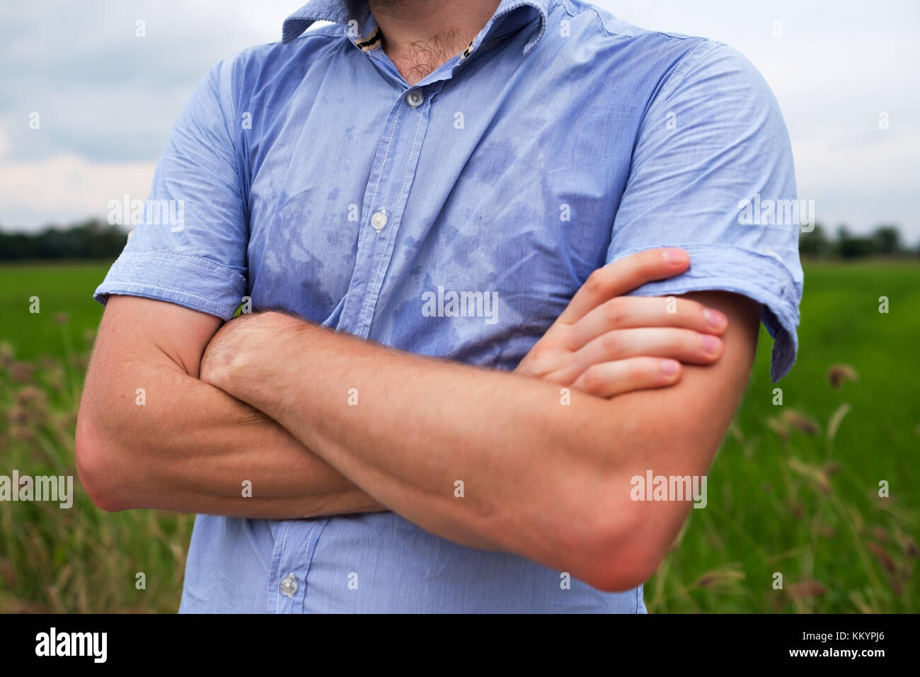 Man with hyperhidrosis sweating very badly under armpit in blue shirt, isolated on grey - Stock Image