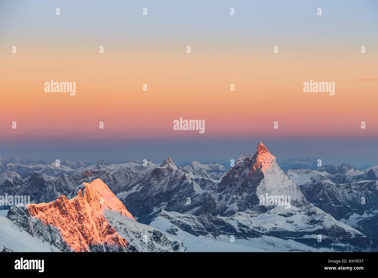 Pink sunset light on Matterhorn as seen in summer from Margherita Hut with snowy mountains around - Stock Image