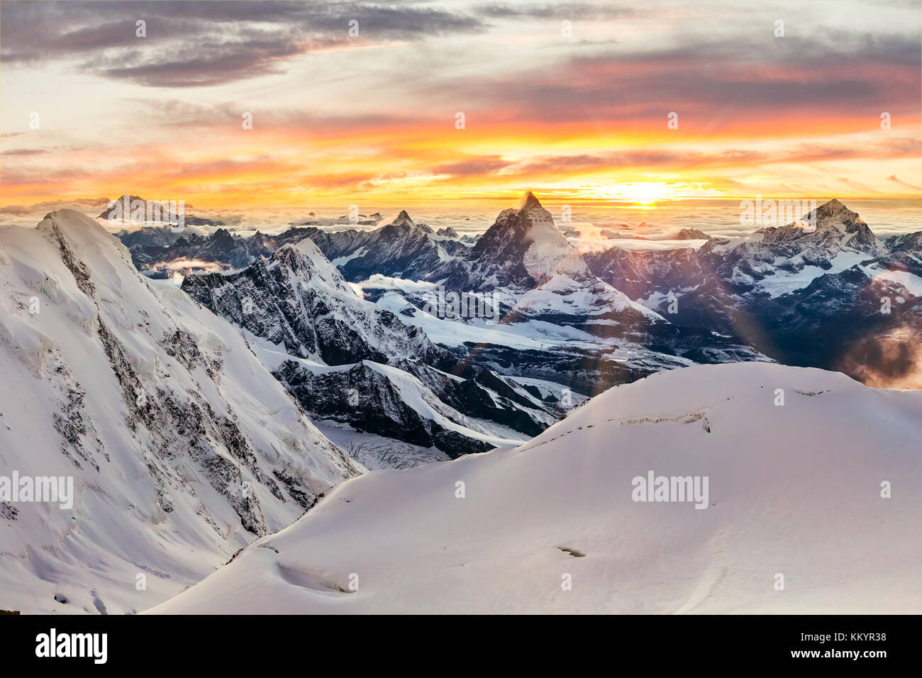 Sun setting behind the Matterhorn as seen form Monte Rosa, with mountains covered in snow - Stock Image