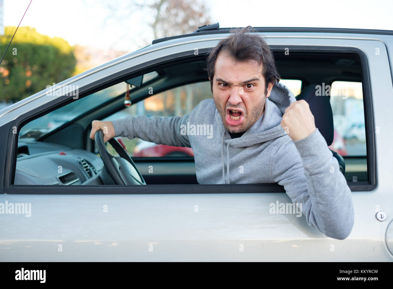 Portrait of angry driver at the wheel. Negative human emotions face expression - Stock Image