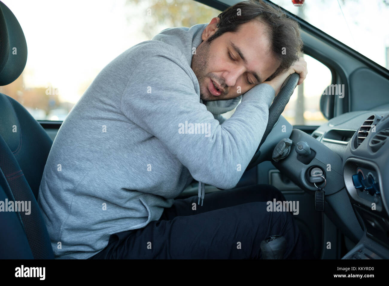 Sleepy yawning man driving car in traffic after long hour drive - Stock Image