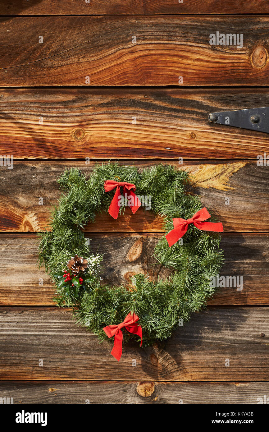 Christmas Wreath on a barn wood wall - Stock Image