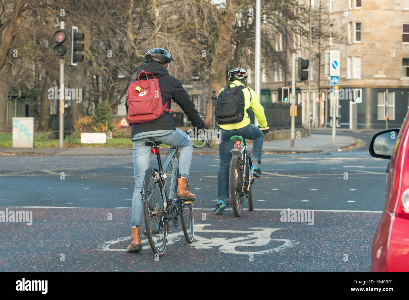 cyclists using bike box with advanced stop line on road at traffic lights in Edinburgh city centre, Scotland, UK - Stock Image