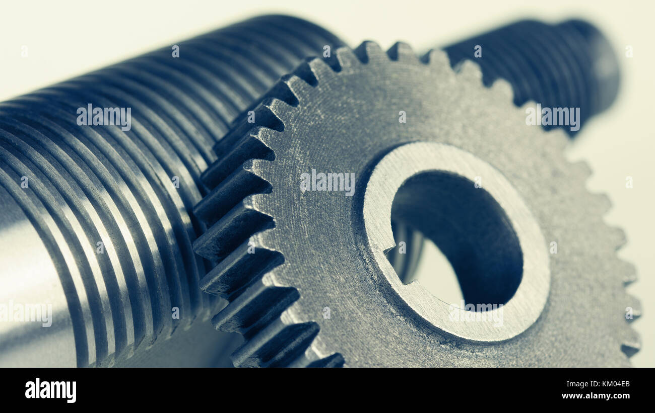 Close-up of steel gearwheel and shaft with thread. Abstract engineering background with cogwheel and bolt. - Stock Image
