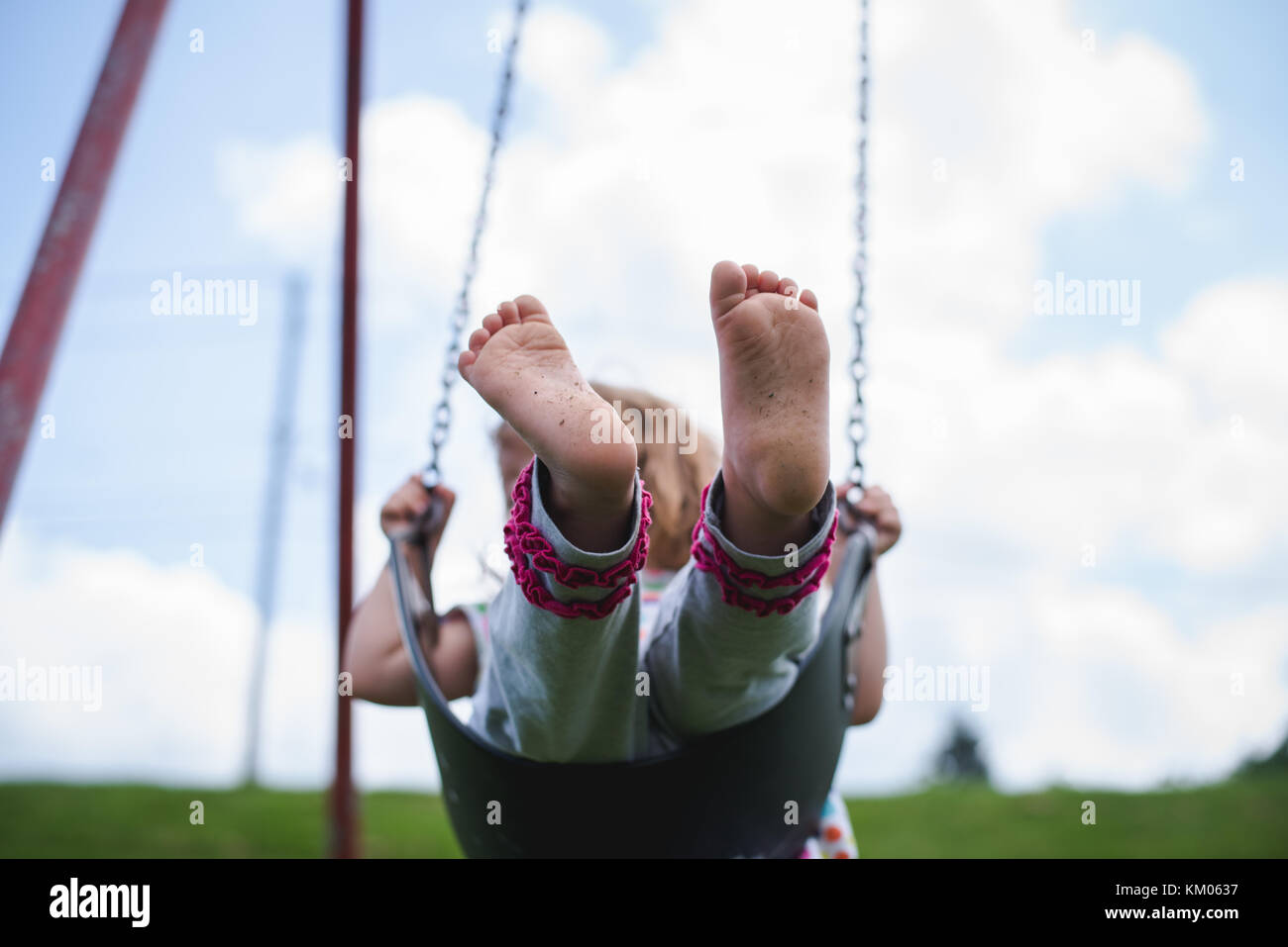 A young girl swings on a swing at a playground in bare feet. - Stock Image