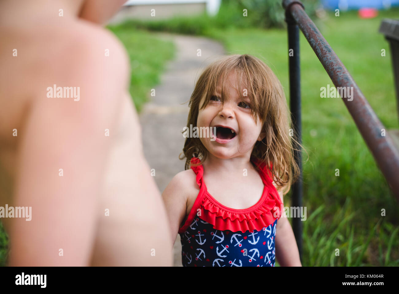 A toddler cries while her brother looks on. - Stock Image