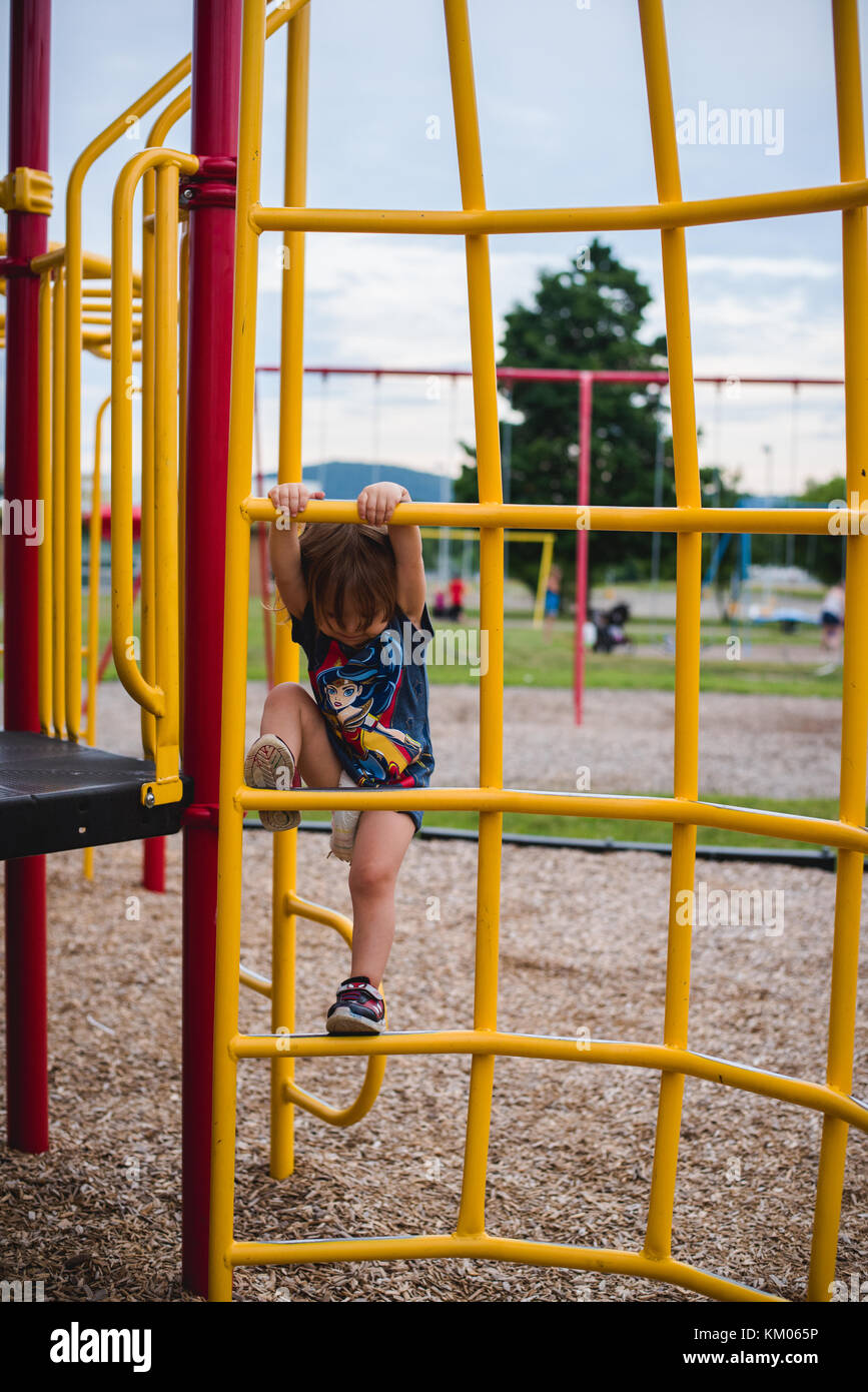 A toddler climbs at a playground, - Stock Image