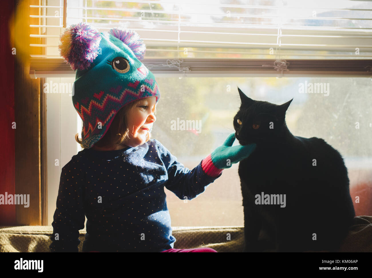 A little girl wearing a winter hat pets a cat while sitting in a sunny window. Stock Photo