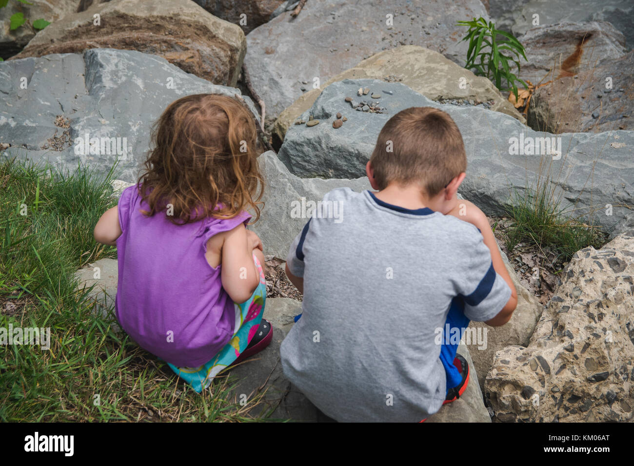 A brother and sister sitting next to each other with their backs to the viewer. - Stock Image