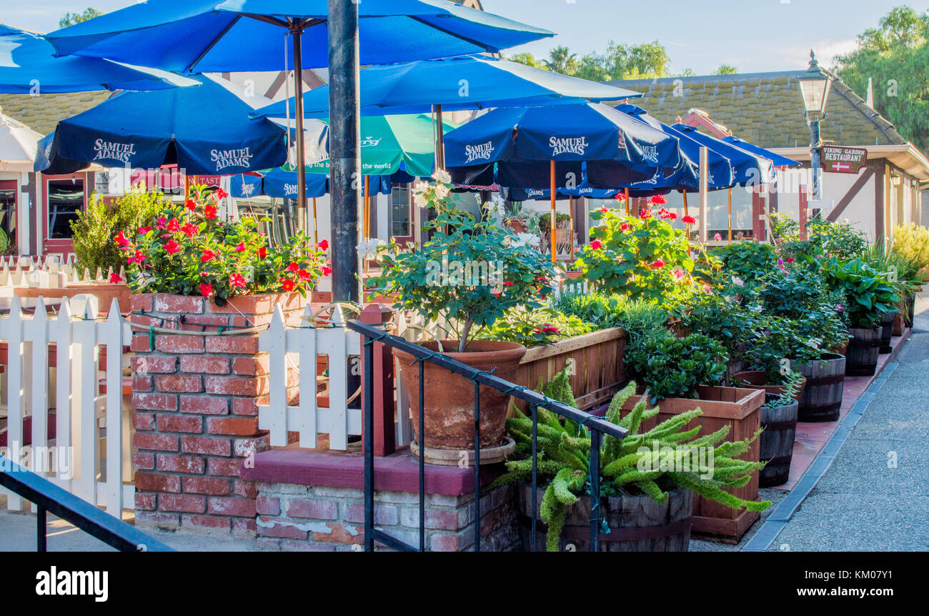 outdoor courtyard restaurant under blue umbrellas with early morning sunlight in Solvang, California, US - Stock Image