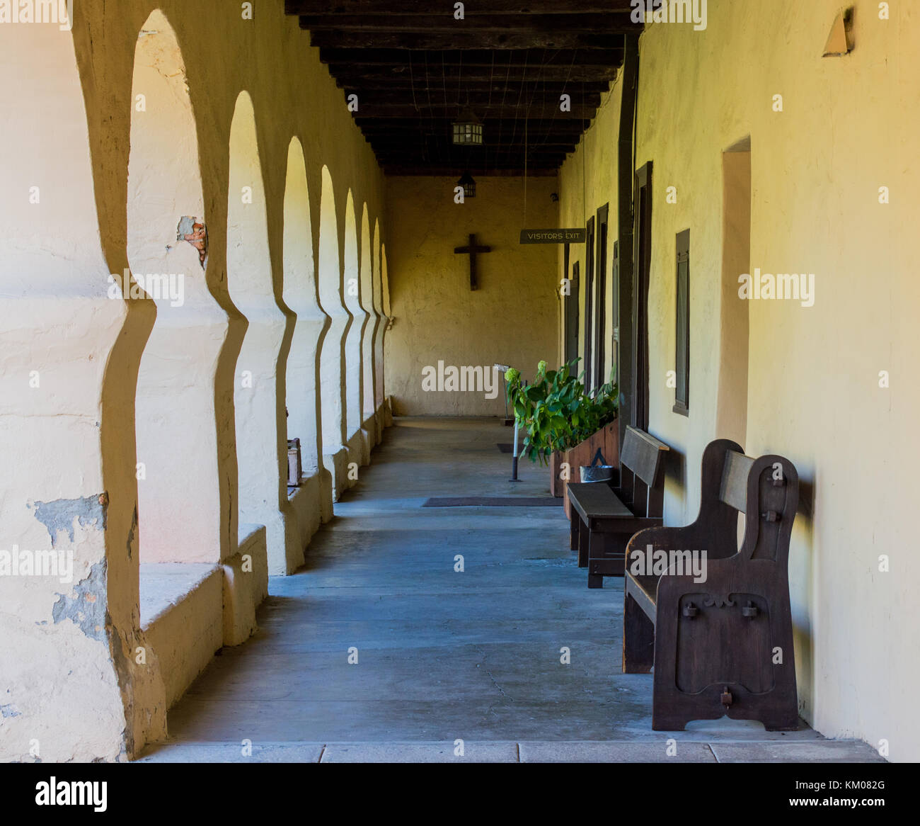 arched outdoor walkway and brown benches at a California mission with early morning sunlight - Stock Image