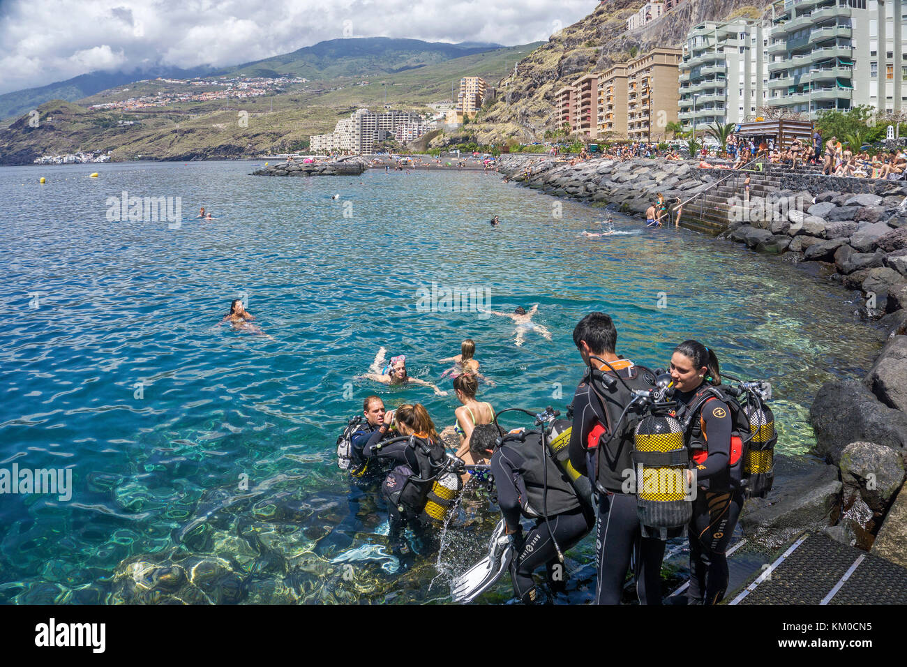 A group scuba diver entering water at Radazul, south-east of Tenerife island, Canary islands, Spain - Stock Image