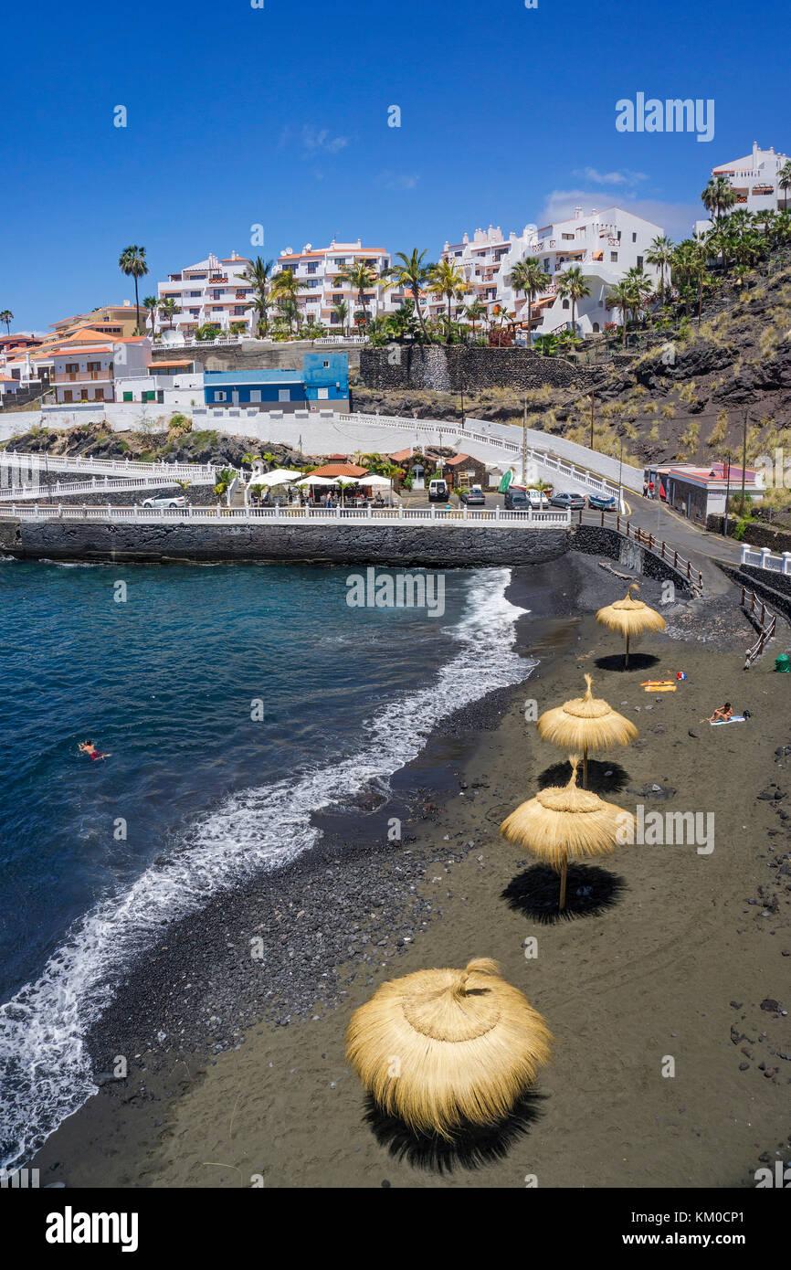 Piscina los chocos, tiny dark colour beach at village Puerto de Santiago, west coast of Tenerife island, Canary - Stock Image