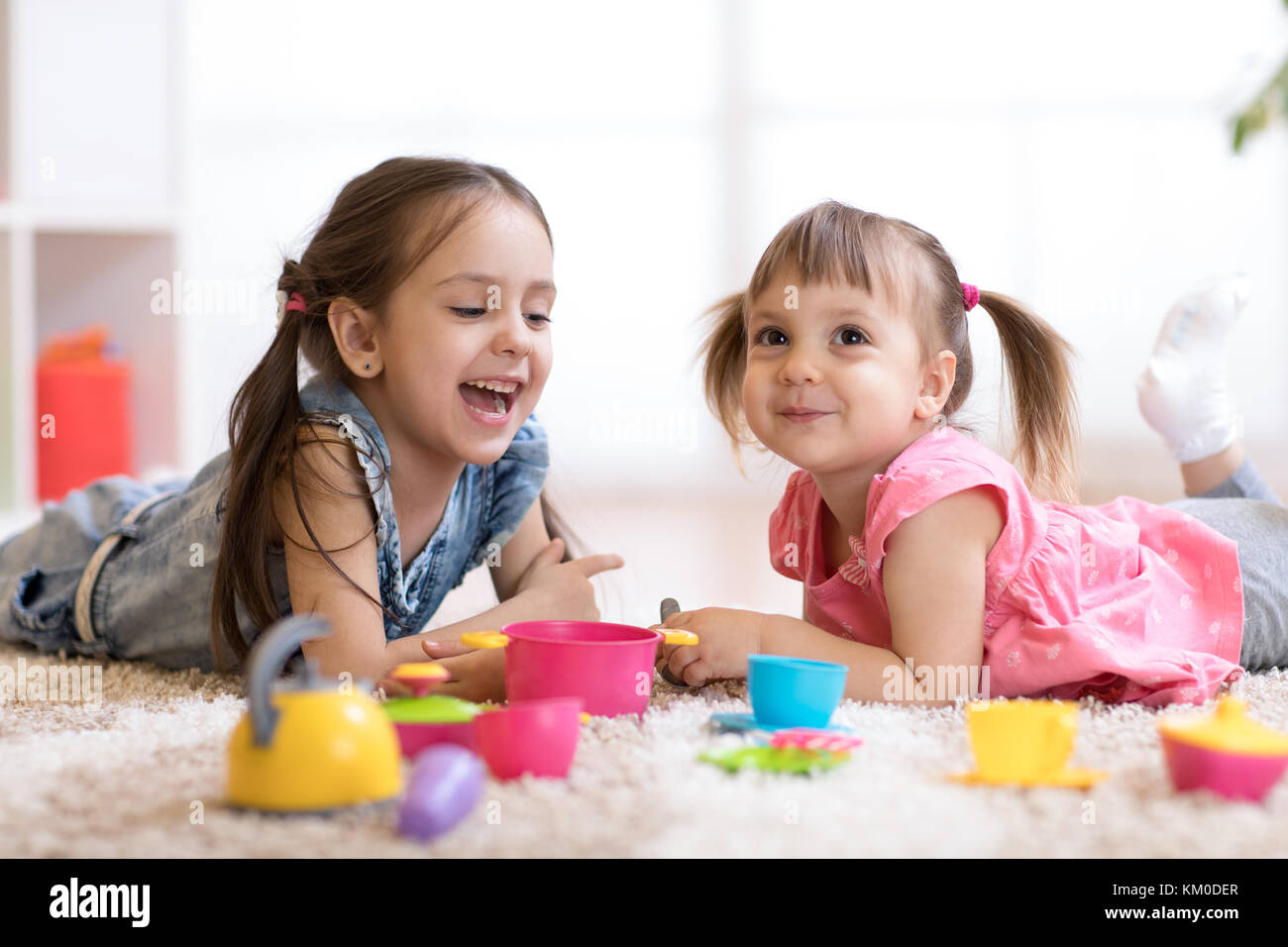 Cute little children playing with kitchenware while lying on floor at home - Stock Image