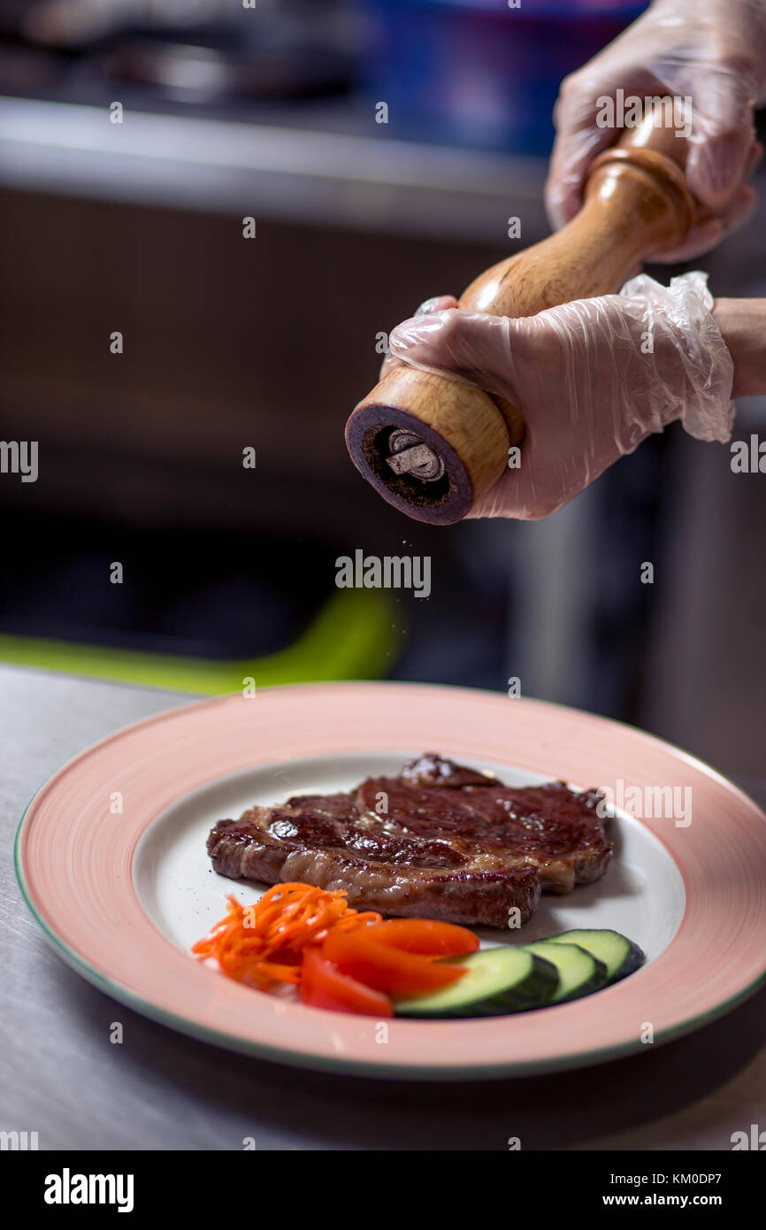 Chef in restaurant kitchen cooking, hands to be seen, he is seasoning dishes - Stock Image