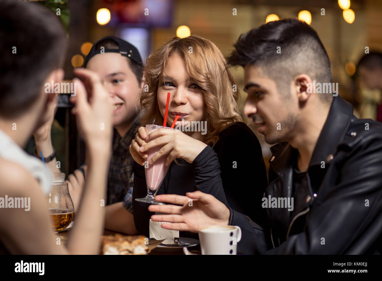 Young woman drinking milkshake while sitting with friends at cafe - Stock Image
