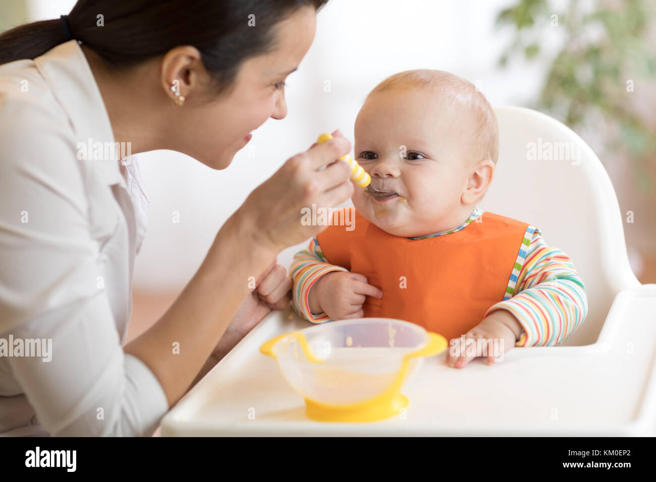 Food, child and parenthood concept - mom with puree and spoon feeding baby at home - Stock Image