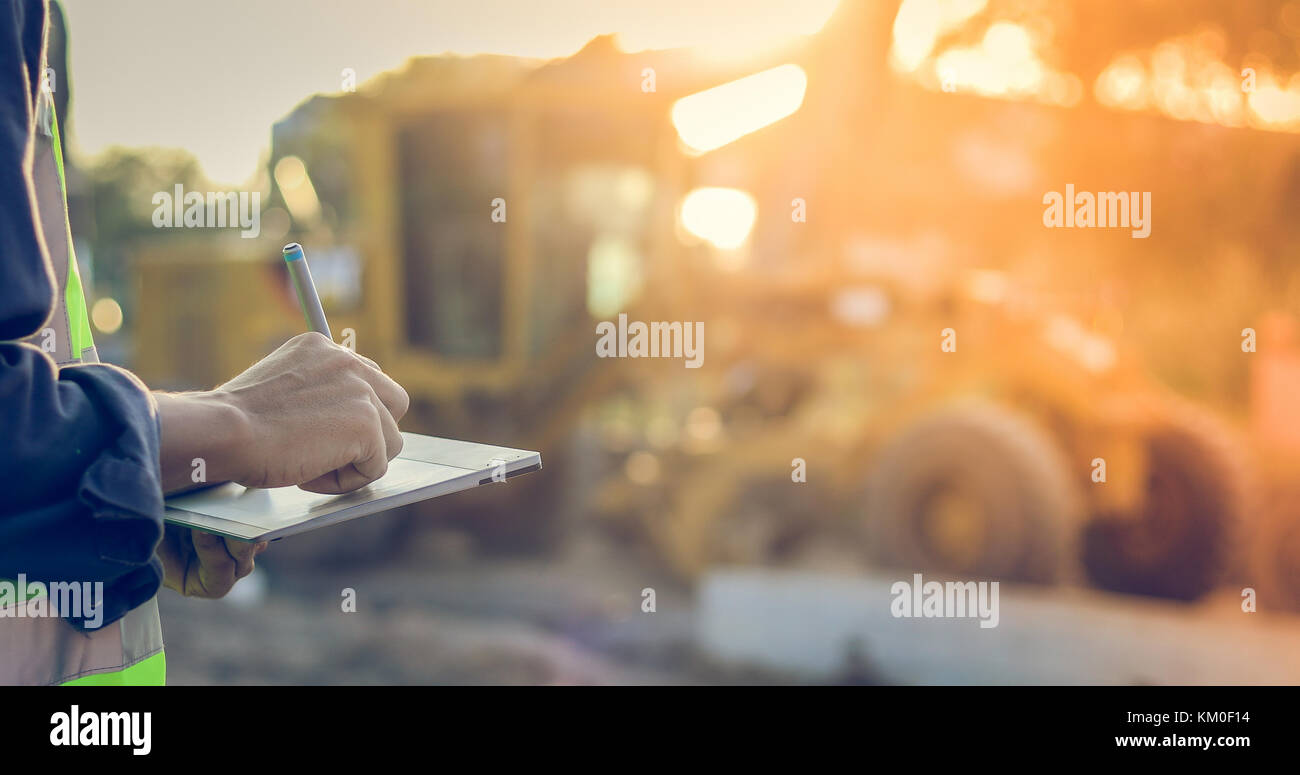 Asian engineer with hardhat using  tablet pc computer inspecting and working at construction site - Stock Image