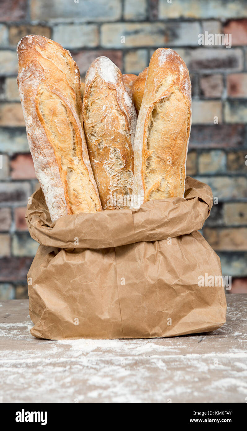 the fresh baked rustic bread loaves in paper bags