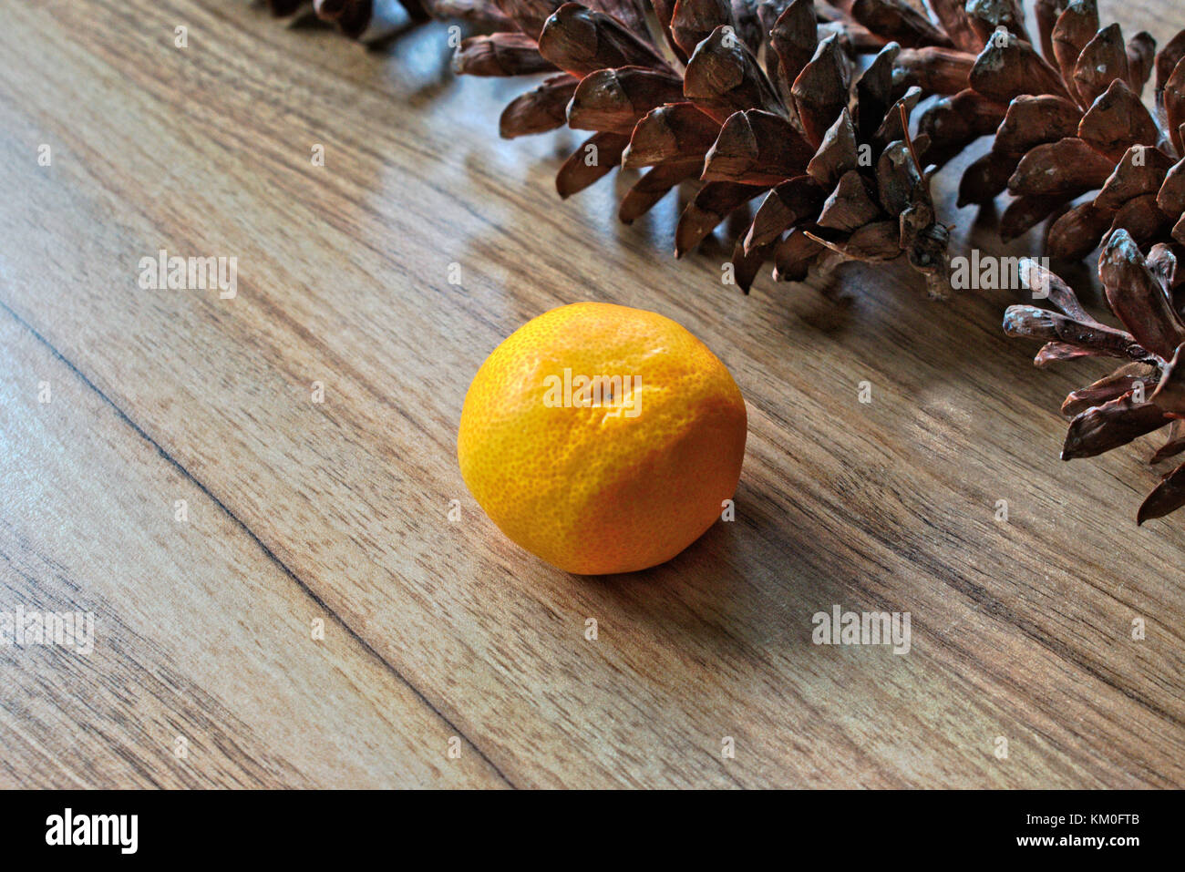 Tangerine and pine cones on a wooden table - Stock Image