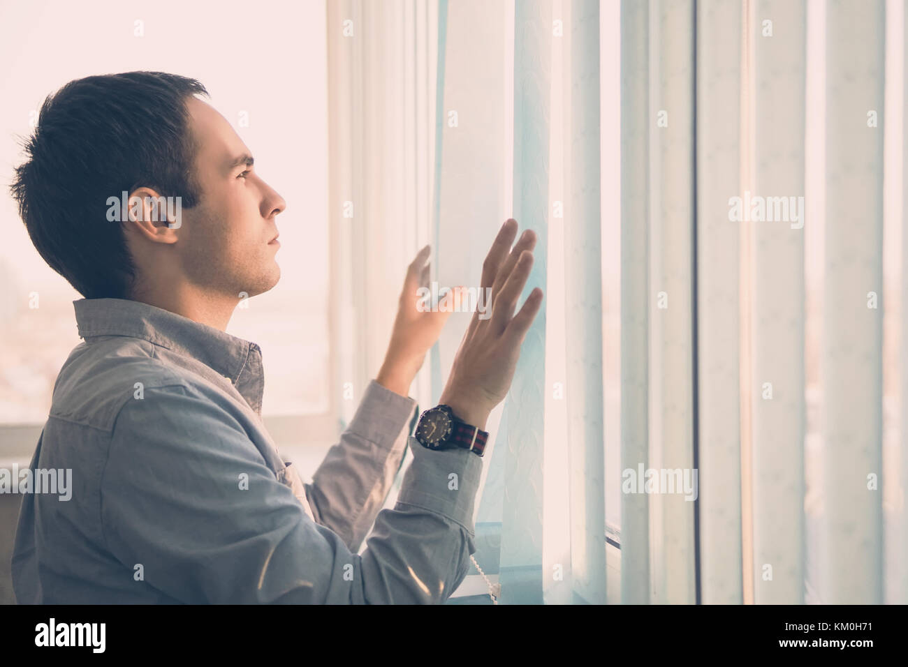 Young businessman standing in modern office, looking through blind, thinking. Vertical blinds light blue color on - Stock Image