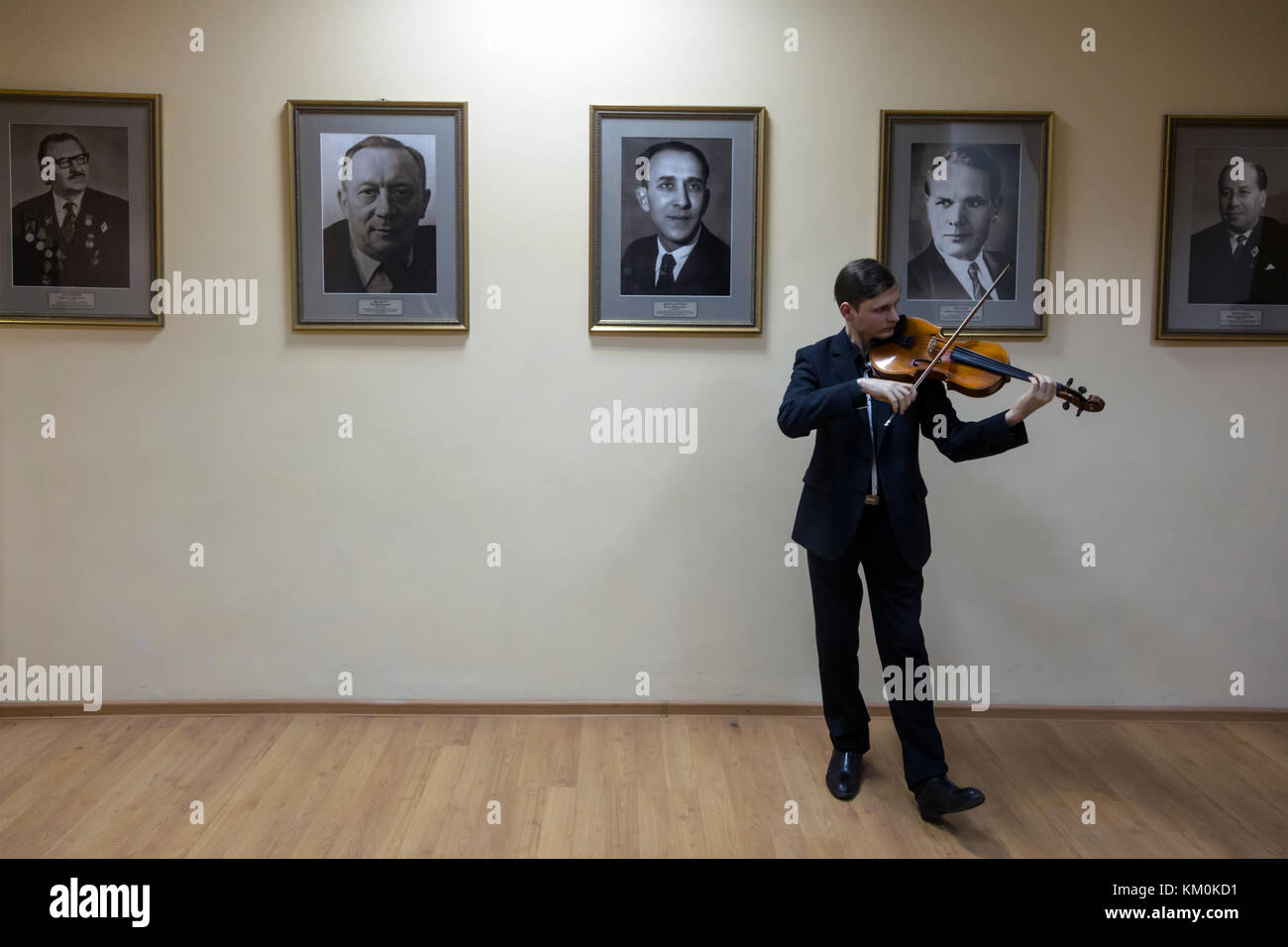 A student rehearses on a violin in the Gnesins Russian Academy of Music against the background of portraits of famous Stock Photo