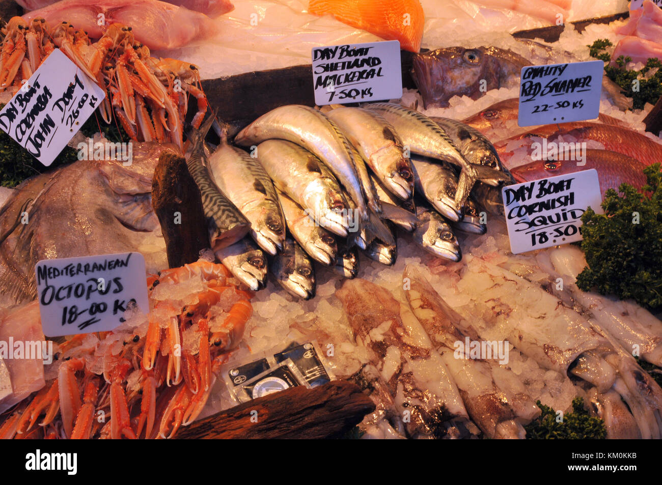 A selection of fresh fish on a wet fish stall at a fishmongers on borough market in Southwark, London. Fresh oily - Stock Image