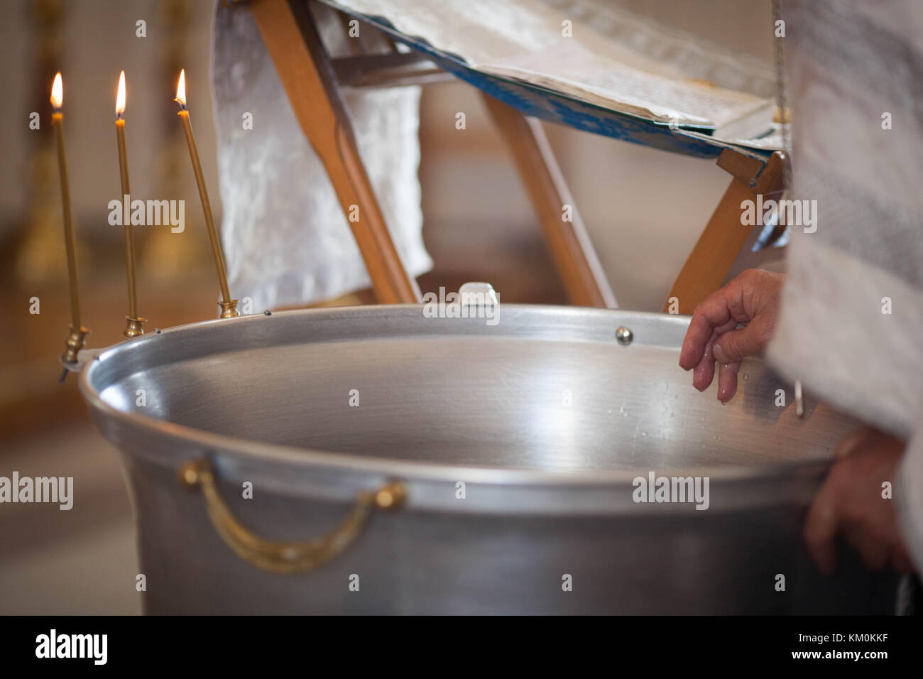 Orthodox baptism bowl of holy water and candles. - Stock Image
