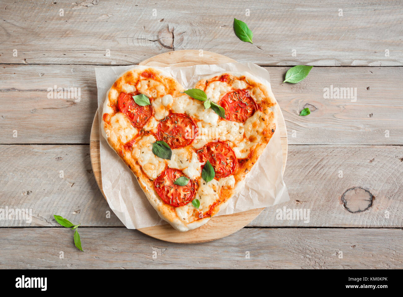 Heart shaped pizza Margherita over wooden background with copy space. Pizza with tomatoes, mozzarella cheese and - Stock Image