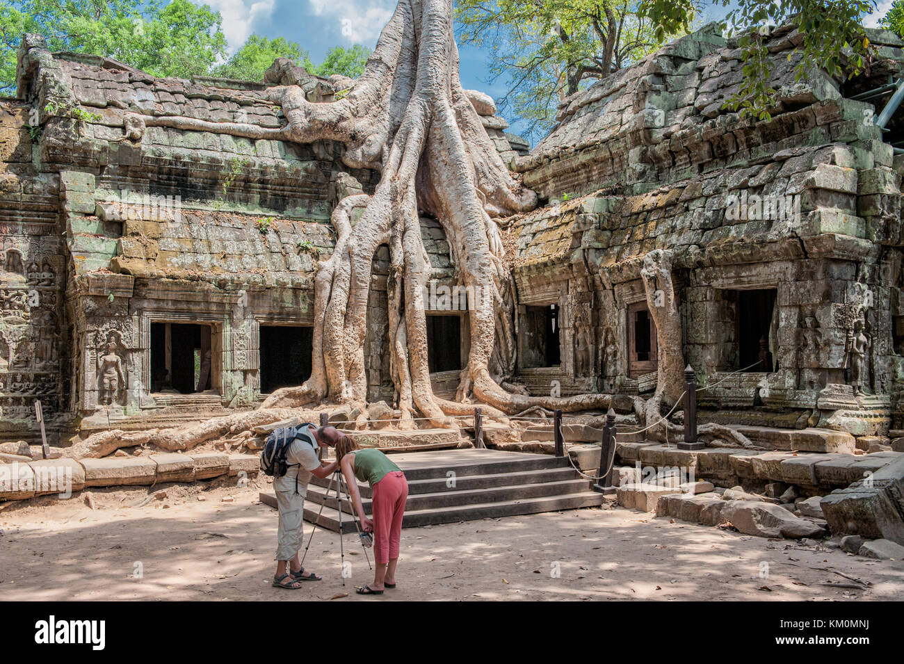 Tourists posing at Ta Prohm in Siem Reap. Built in 12-13th century Ta Prohm temple was later the location for the - Stock Image