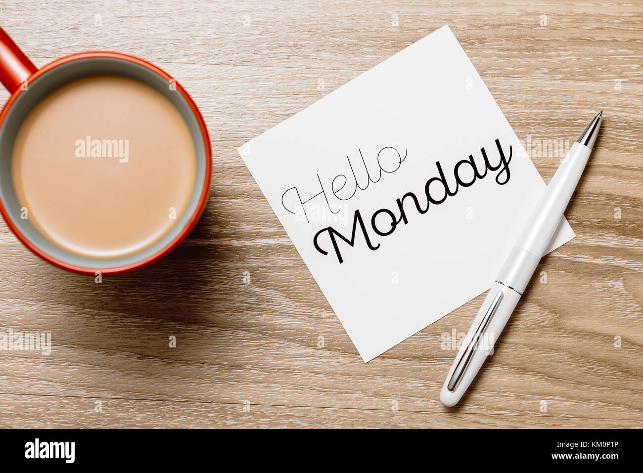 Good morning Monday - cheerful message on a sticky note with a cup of coffee and pen - Stock Image