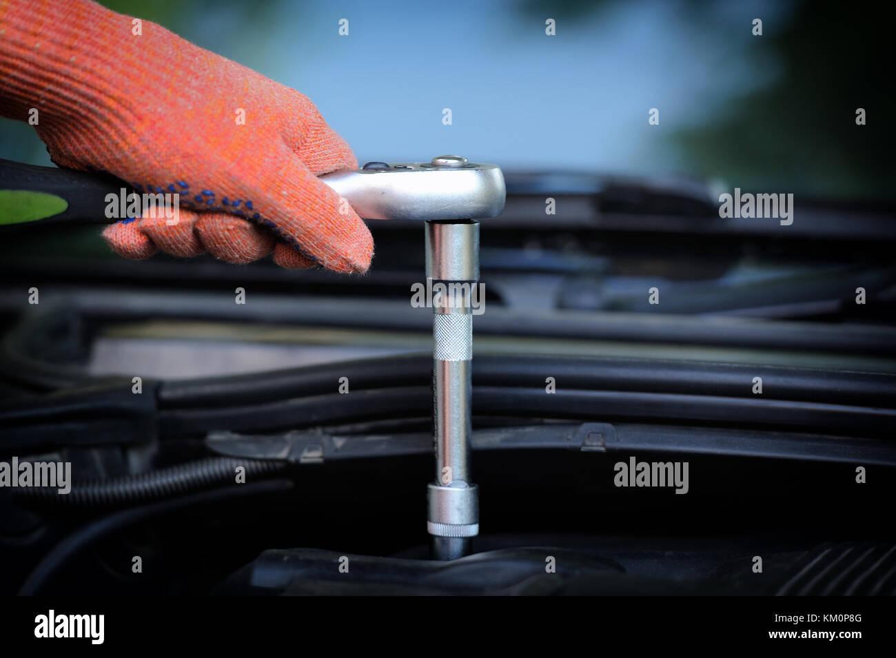 Hands of car mechanic in auto repair service - Stock Image
