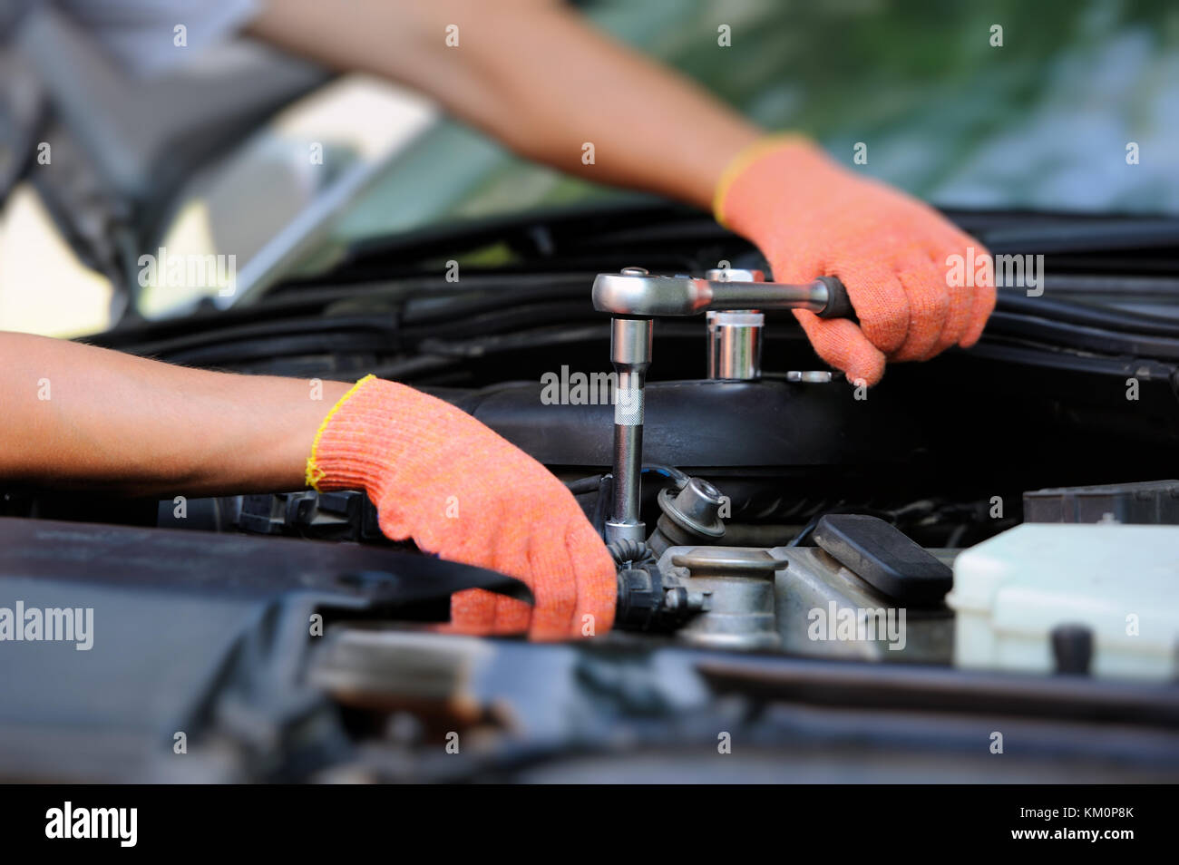 Hands of car mechanic in auto repair service - Stock Image