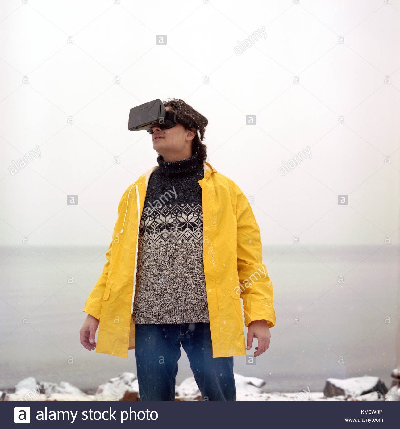 Mixed race latin hispanic man in yellow coat enjoying virtual reality glasses headset or 3d game outdoors at winter - Stock Image