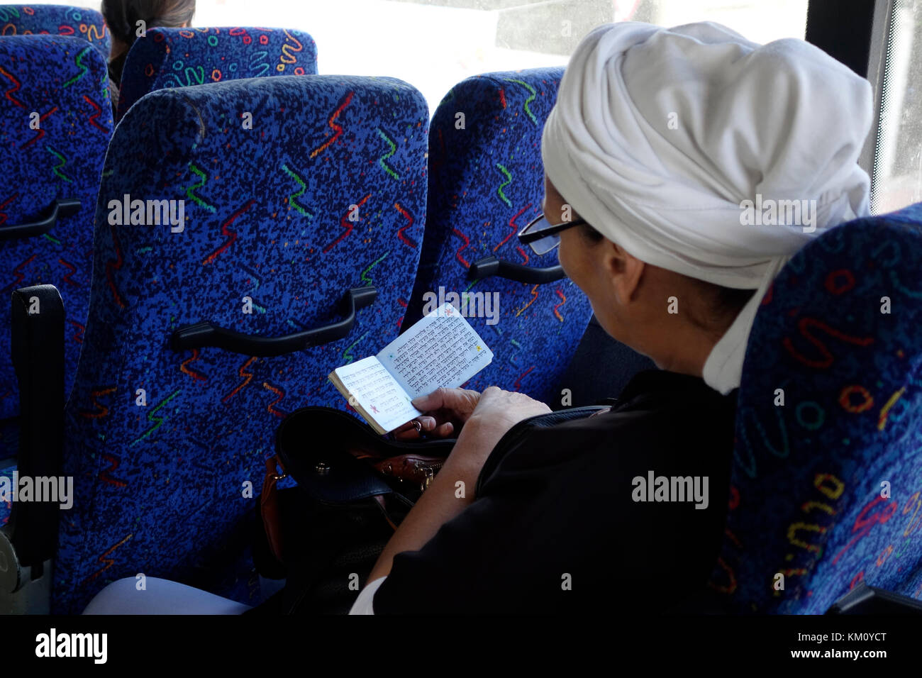 A religious Jewish woman reading a Jewish daily prayer book in Hebrew in a bus in Israel - Stock Image