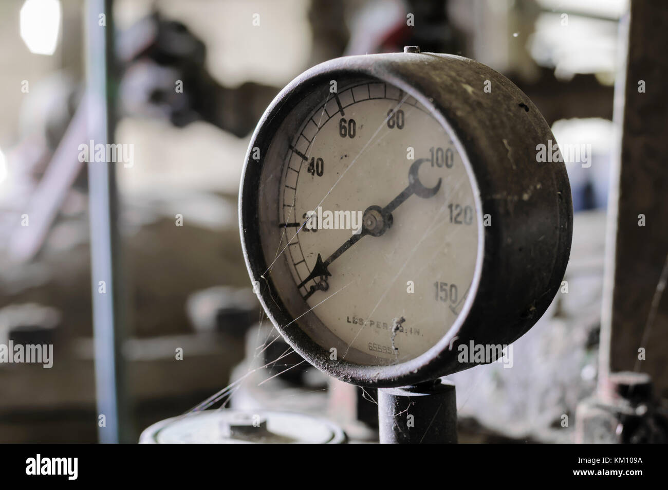 Old pressure gauge on a pump manufactured around 1940. - Stock Image