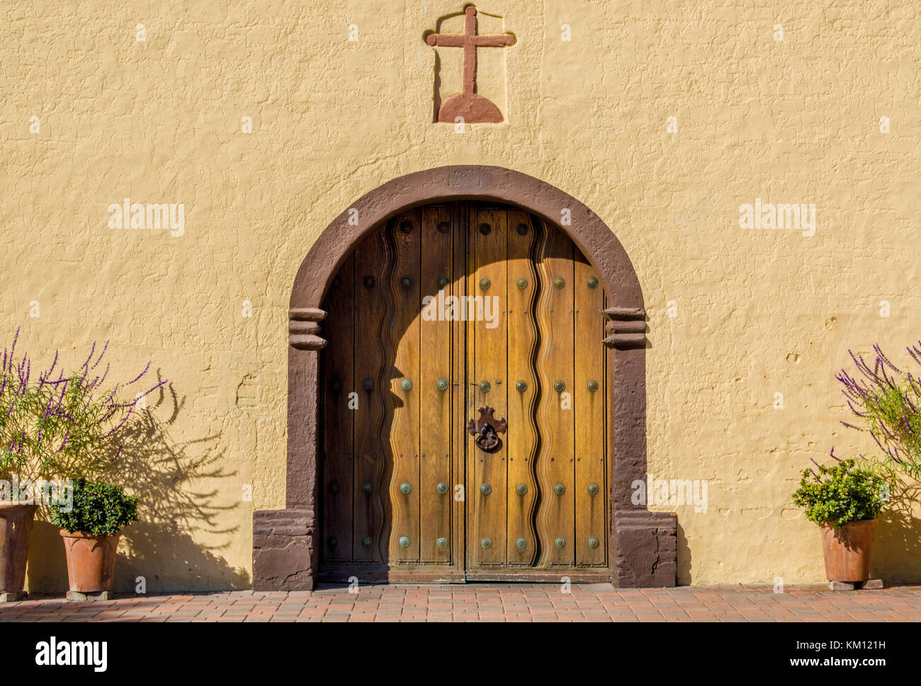 arched wooden door with a cross above it at the entrance to an adobe  church in early morning sunlight with shadow - Stock Image