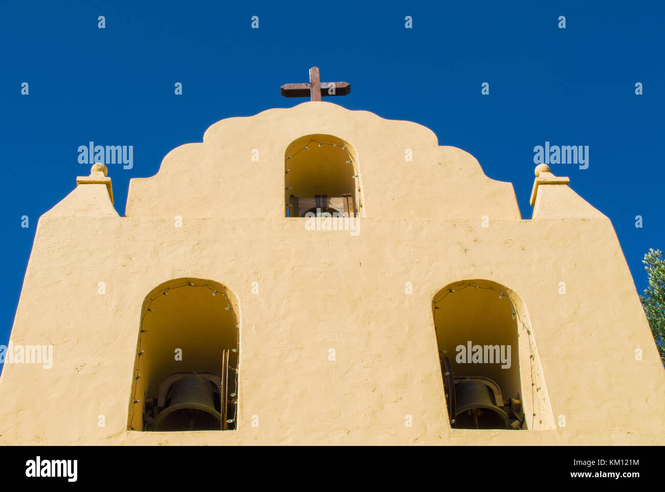 adobe mission bell tower with cross at top viewed from below - Stock Image